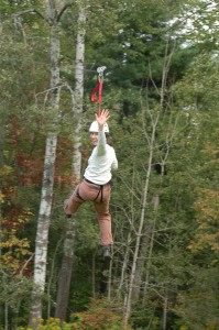 Photo of Krista riding the zipline at Camp Bryn Mawr in Wayne County, PA on team building day.