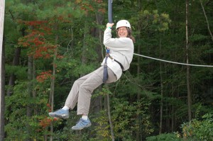 Photo of Sandy riding the giant swing at Camp Bryn Mawr near Honesdale, PA on team building day.